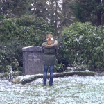 Frau steht vor Grab