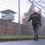 Mann vor Gefängnismauern