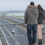 Ehepaar steht auf Autobahnbrücke