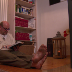 Mann sitzt lesend vor Kamin